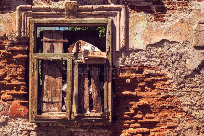 Venster van een verlaten huishoogtepunt van huisvuil stock foto's