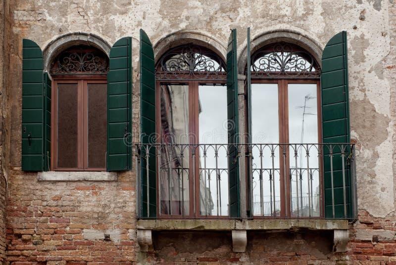 Vensters met groene blinden van Venetië, Italië stock afbeeldingen