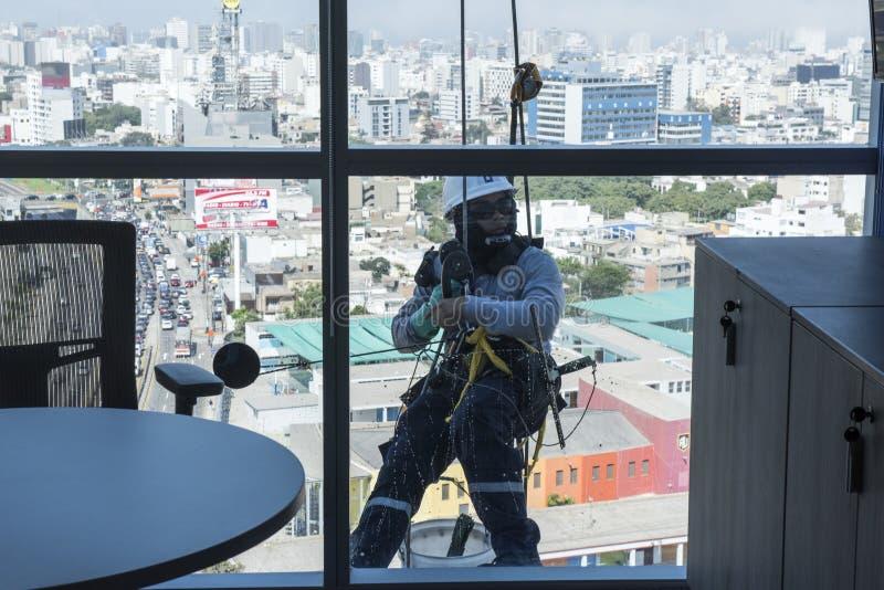 Vensterwasmachines die de glasvoorgevel van een modern gebouw, het zeer riskante werk schoonmaken stock fotografie