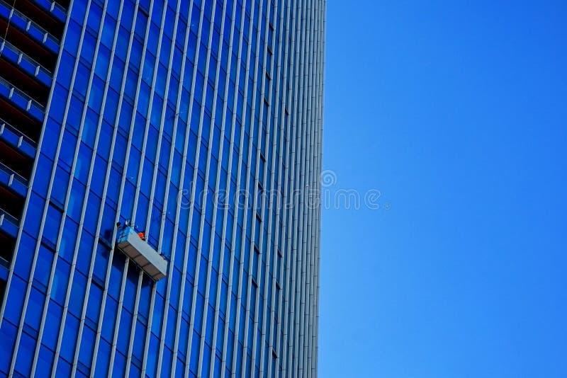 Vensterwasmachines die van de kant van een gebouw hangen die enkel hun werk doen stock foto's