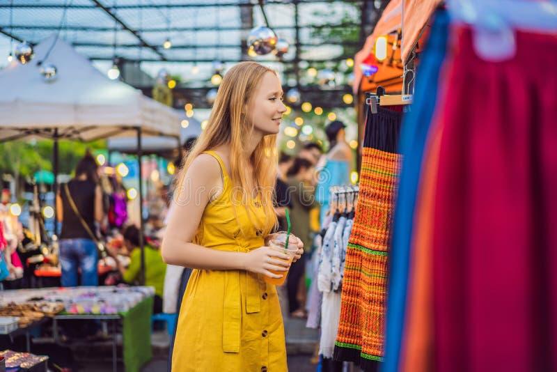 Venta, venta al por menor, compras y concepto de la ropa - la mujer elige la ropa en el mercado asi?tico imágenes de archivo libres de regalías