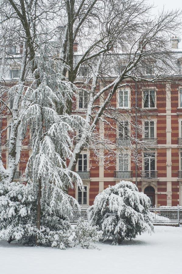 Venta al por menor del jardín público con nieve en árboles con el edificio antiguo fotos de archivo libres de regalías