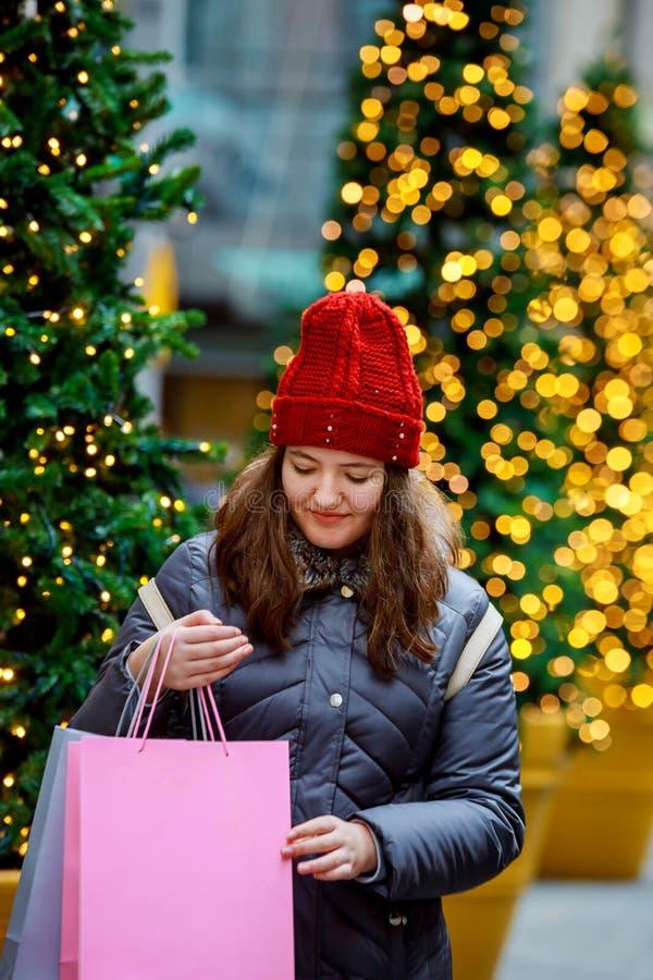 venta, chica joven feliz con los bolsos de compras que camina a lo largo de la calle de la ciudad, fondo colorido del bokeh de la imagenes de archivo