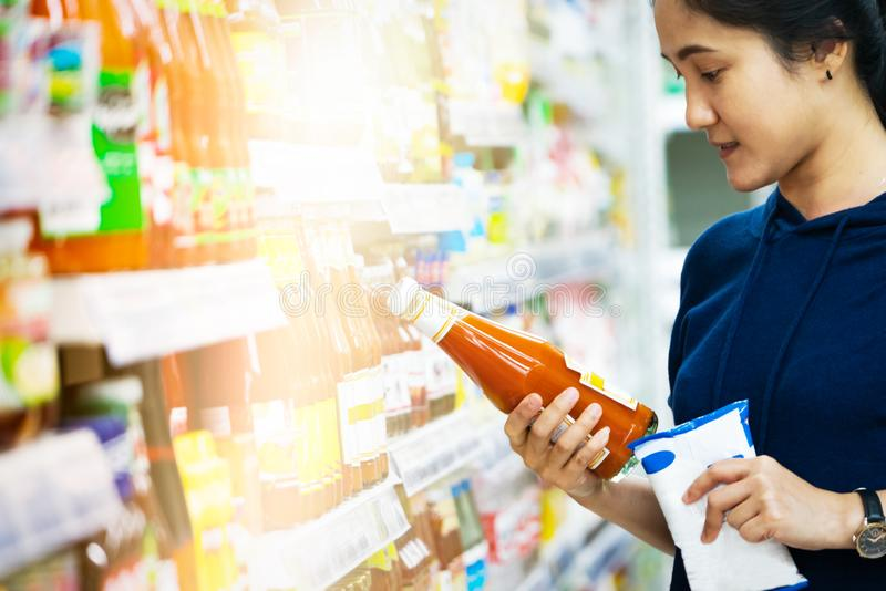 Venta, compras, consumidor, mujer que elige mercancías en el colmado o la tienda del supermercado imagenes de archivo