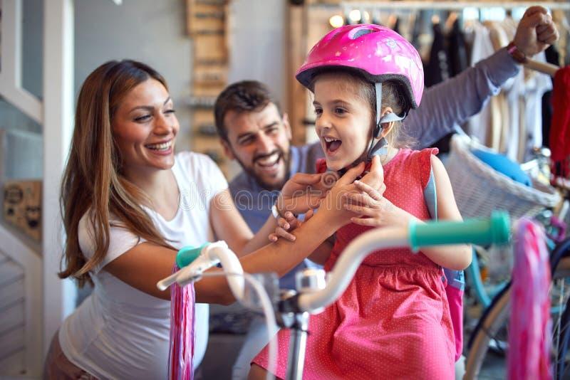 Venta, consumerismo y concepto de la gente - mujer que elige la nuevos bicicleta y casco para la ni?a en tienda de la bici imagenes de archivo