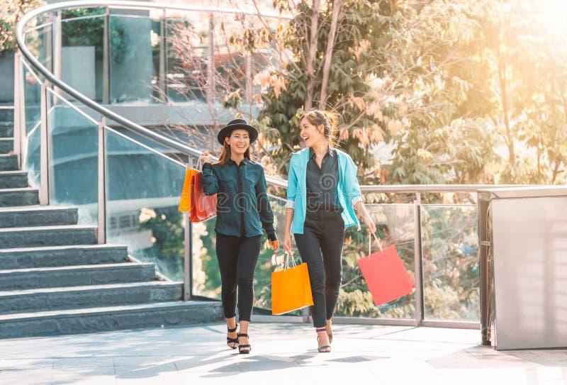 Venta, consumerismo y concepto de la gente - mujeres jovenes felices que miran en los panieres la tienda en ciudad fotos de archivo libres de regalías