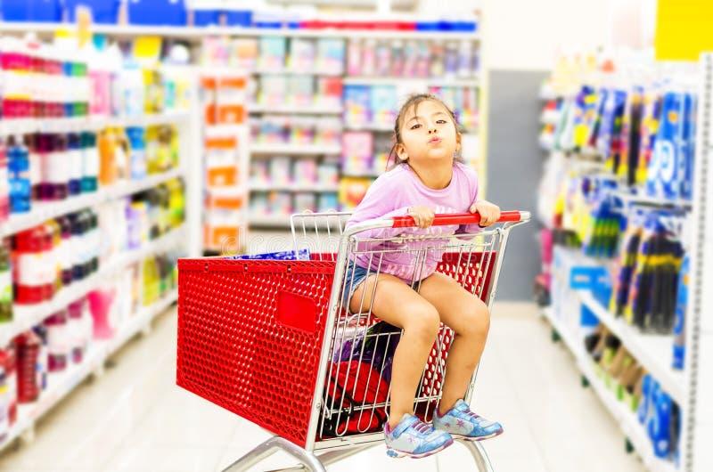 Venta, consumerismo y concepto de la gente - ni?a feliz en carro de la compra imagen de archivo