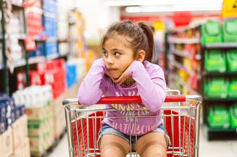 Venta, consumerismo y concepto de la gente - ni?a feliz pensativa en carro de la compra foto de archivo libre de regalías