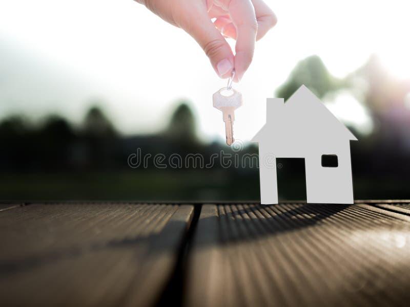 Venta de concepto de las propiedades inmobiliarias con la casa y de llave del agente inmobiliario foto de archivo libre de regalías