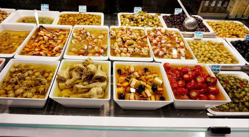 Venta de la comida en placas plásticas en el mercado de Boqueria en Barcelona fotografía de archivo