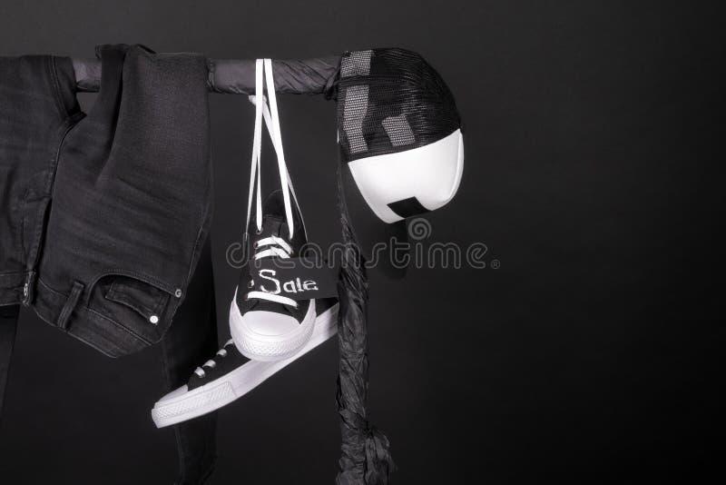 Venta rosada y amarilla Las zapatillas de deporte blancos y negros, bragas del casquillo, vaqueros que cuelgan en la ropa atormen fotografía de archivo libre de regalías