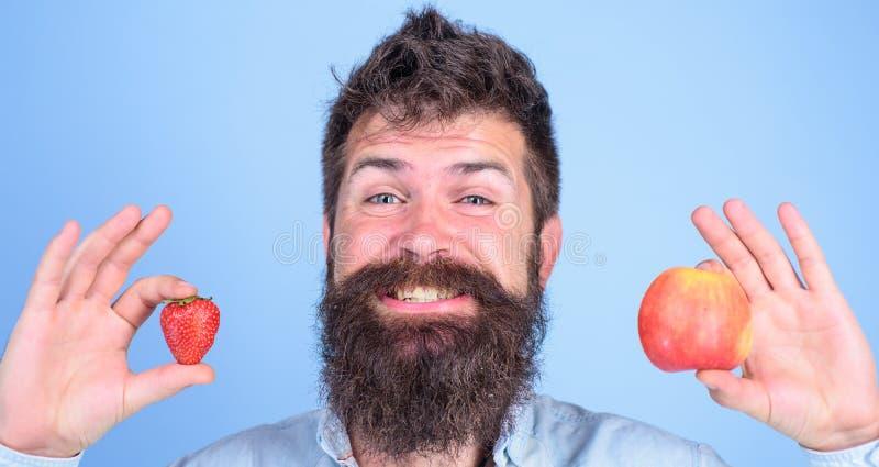 Ventajas del verano Sirva los controles sonrientes barbudos manzana y fresa en fondo del azul de las manos Nutrición de la fruta  imágenes de archivo libres de regalías