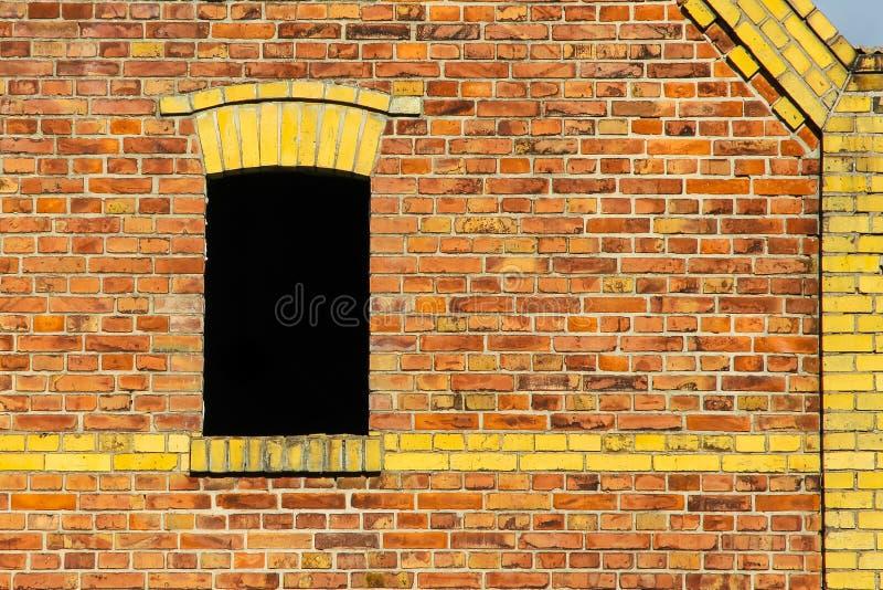 Ventana abierta con el interior del negro oscuro en una pared de ladrillo roja sucia con los detalles amarillos de un granero o d imagen de archivo libre de regalías
