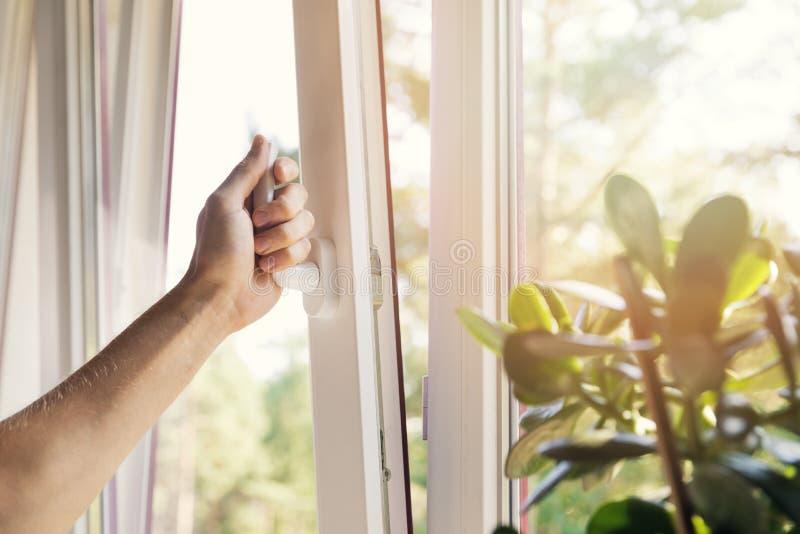 ventana abierta del pvc del plástico de la mano en casa fotos de archivo