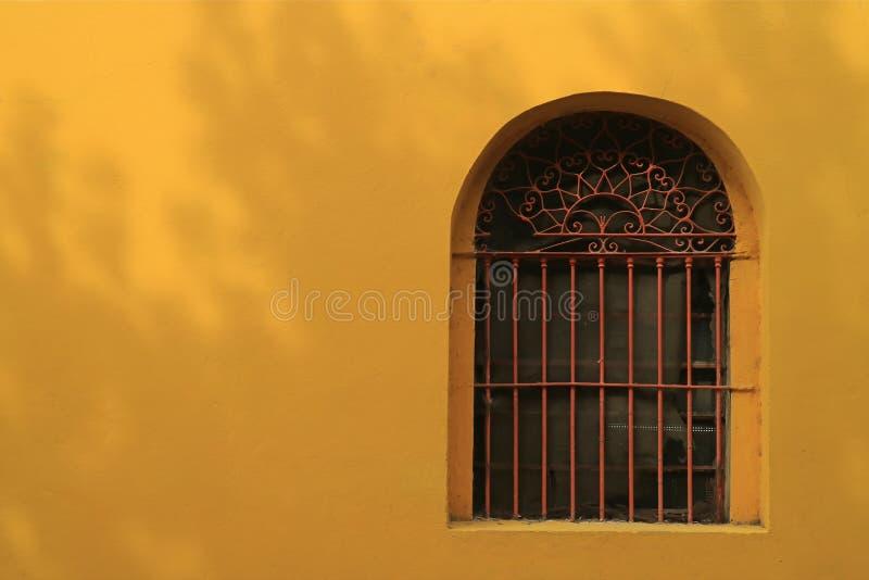Ventana adornada roja del hierro labrado en la pared externa amarilla viva fotos de archivo