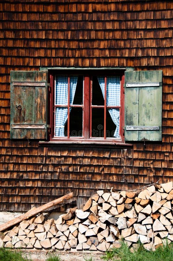 Ventana antigua en la pared de madera de la casa de registro foto de archivo libre de regalías