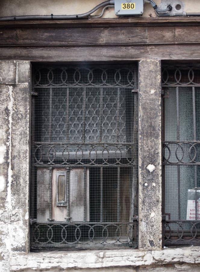 Ventana antigua sucia vieja con las barras foto de archivo