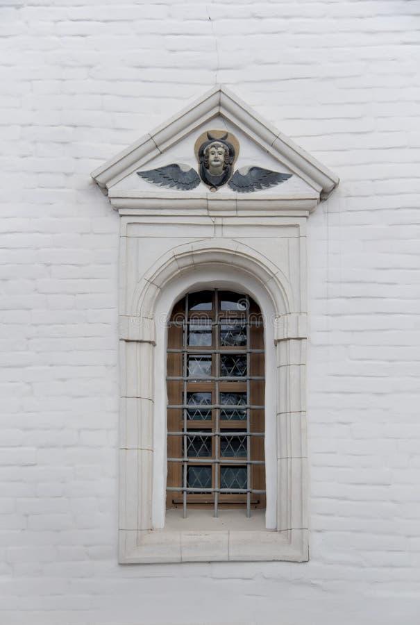 Ventana arqueada vieja con enrejado del metall y alivio en una pared de ladrillo blanca de la iglesia cristiana imagen de archivo