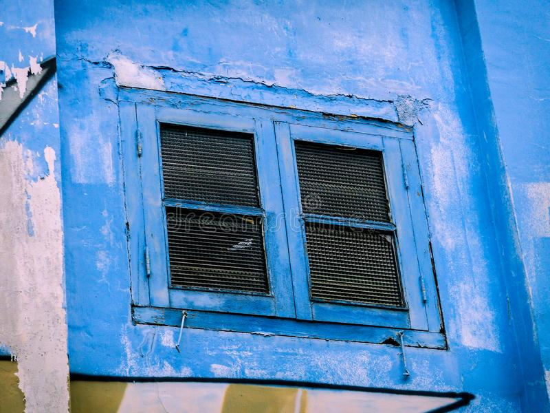 Ventana azul colorida con los obturadores en una calle Art Wall fotos de archivo libres de regalías
