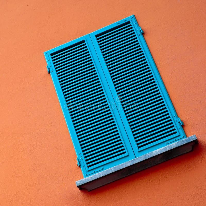 Ventana azul en la pared anaranjada fotos de archivo