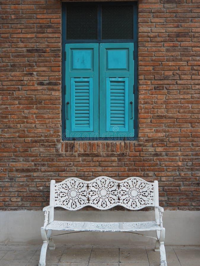 Ventana azul hecha de madera en la pared de ladrillo vieja con el banco del metal blanco imágenes de archivo libres de regalías