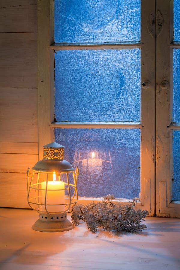 Ventana azul helada y vela ardiente para la Navidad fotografía de archivo libre de regalías