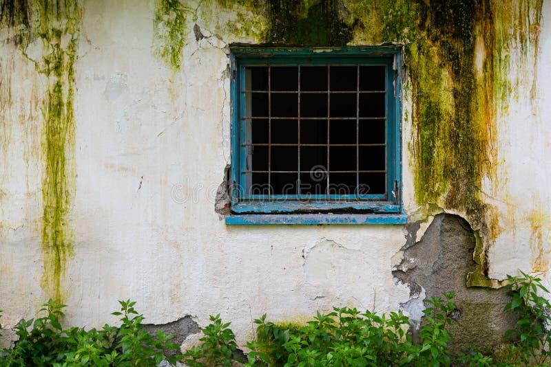 Ventana azul quebrada con el marco metálico en una pared blanca dañada fotos de archivo