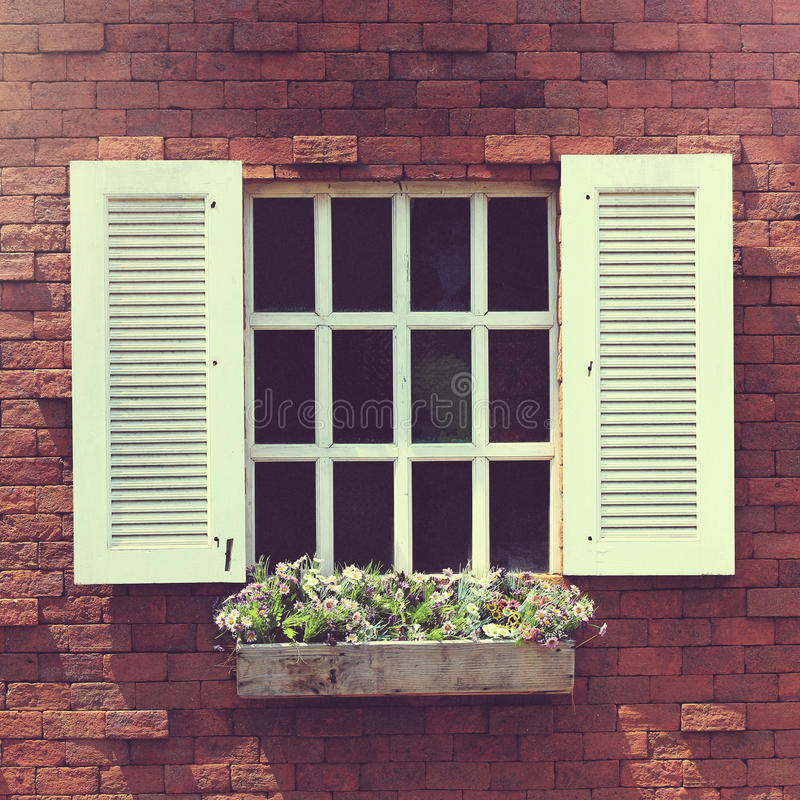 Ventana blanca en una pared de ladrillo con una caja de la flor fotos de archivo libres de regalías