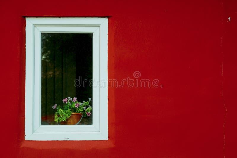 Ventana blanca en una pared roja en la calle fotografía de archivo