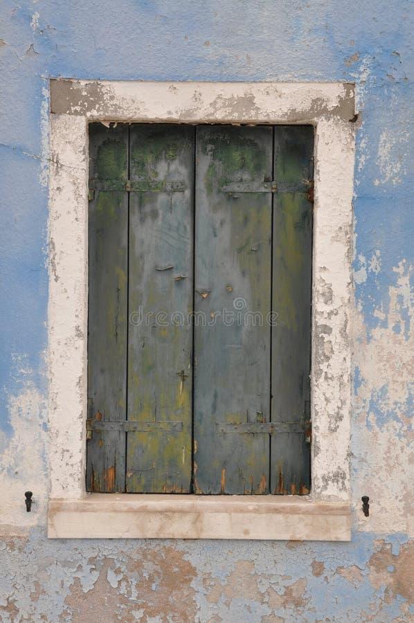 Ventana cerrada con el obturador en la pared azul imagen de archivo