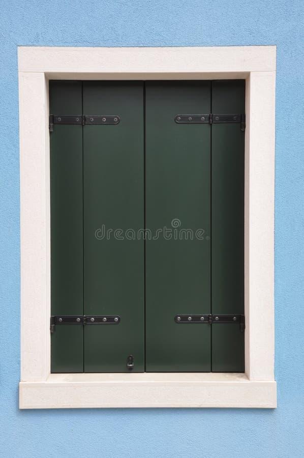 Ventana cerrada con el obturador verde en la pared azul imagenes de archivo
