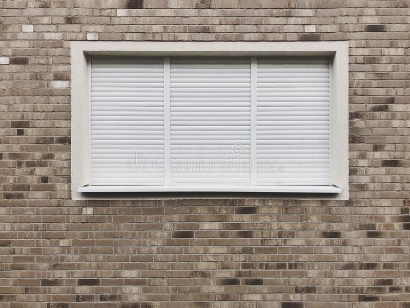Ventana cerrada con las persianas enrrollables o las persianas de rodillo foto de archivo libre de regalías