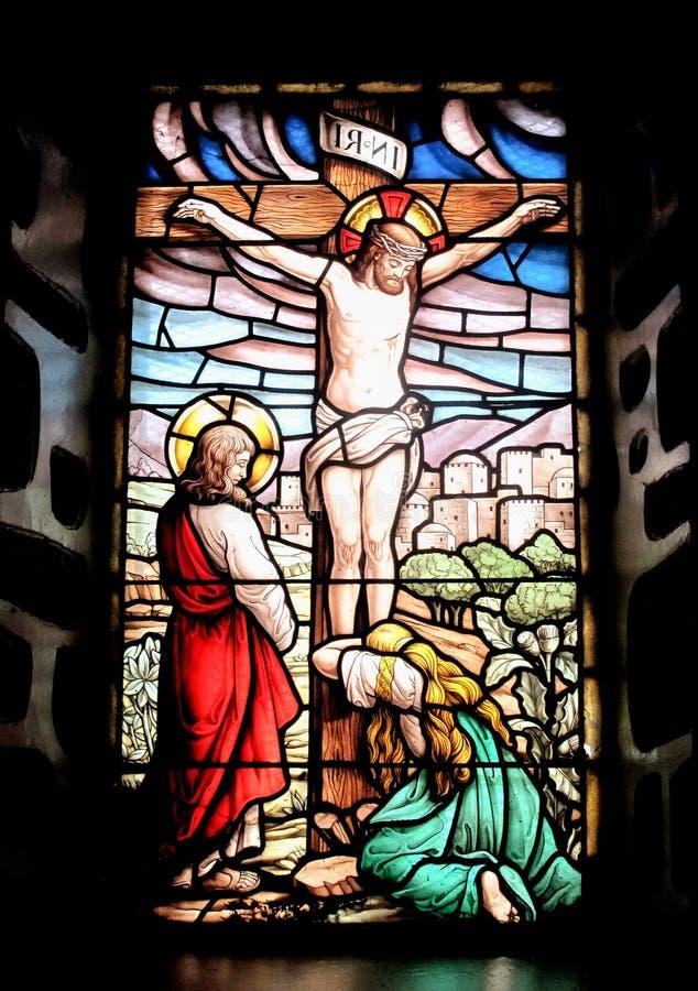 Ventana colorida con la imagen del Jesús crucificado stock de ilustración