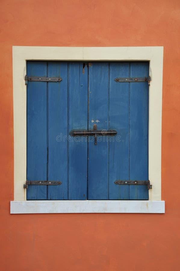 Ventana con el obturador azul en la pared anaranjada imágenes de archivo libres de regalías