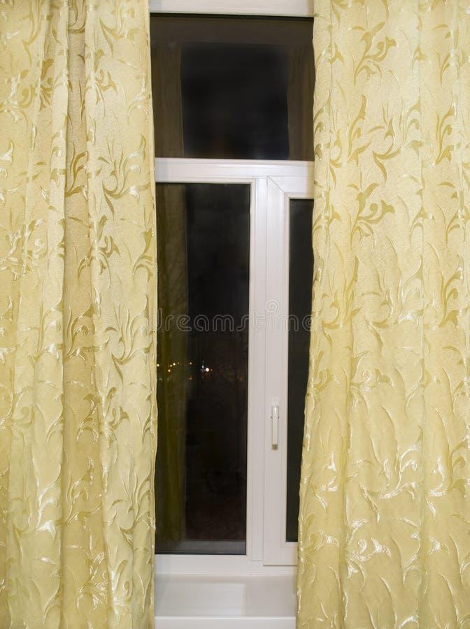 Ventana con las cortinas amarillas fotos de archivo libres de regalías