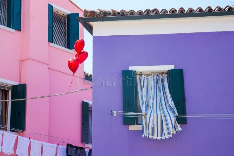 Ventana con las cortinas, los globos en forma de corazón y las casas coloridas en la isla de Burano, Italia fotos de archivo libres de regalías