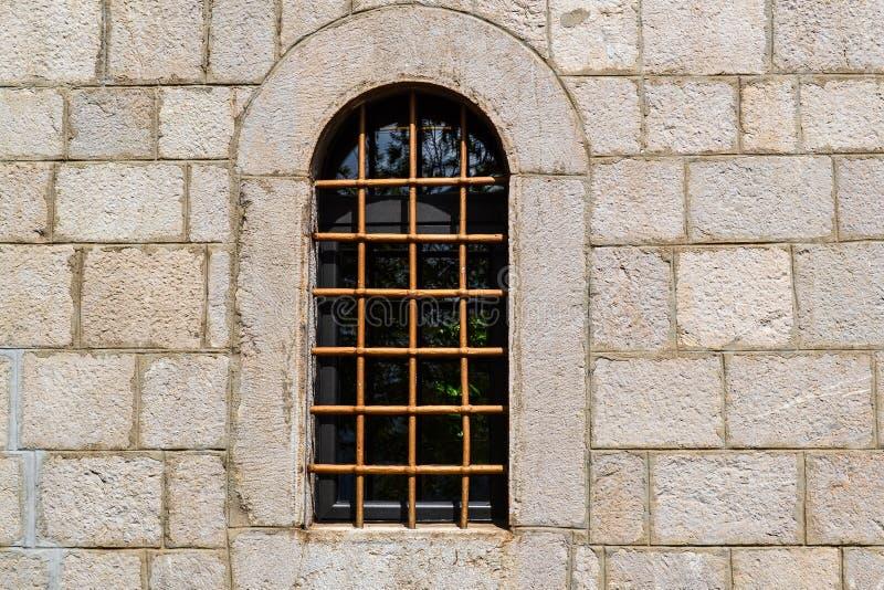 Ventana con un enrejado en la pared de piedra de la fortaleza vieja fotos de archivo libres de regalías