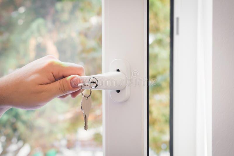 Ventana con una manija bloqueable y las llaves cerradas por una mano masculina, concepto de ventana a prueba de niños imagen de archivo libre de regalías