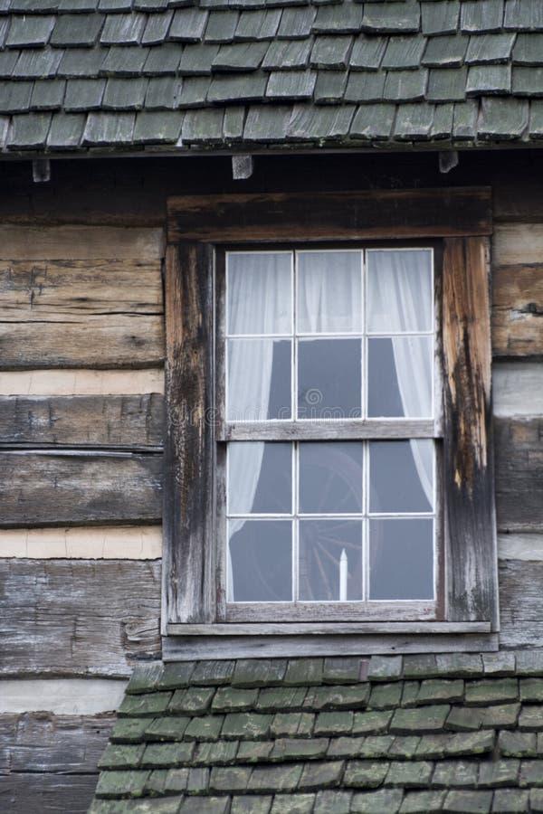Ventana de cabaña de madera con la vela imagenes de archivo
