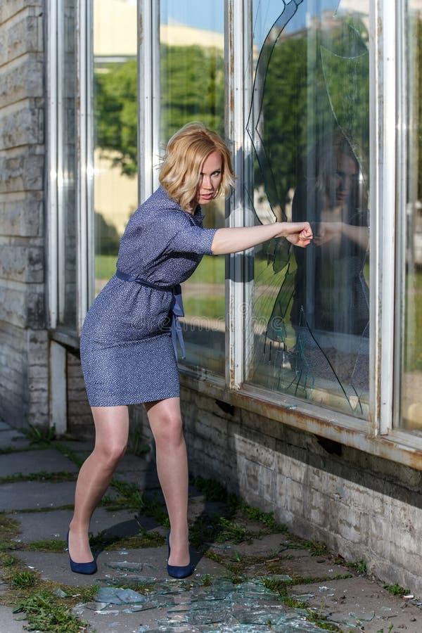 Ventana de cristal de frenado de la mujer muy enojada por su puño imágenes de archivo libres de regalías