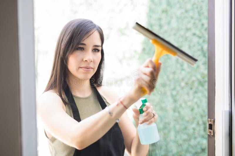 Ventana de cristal de limpieza adorable de la mujer joven con el enjugador imagen de archivo libre de regalías
