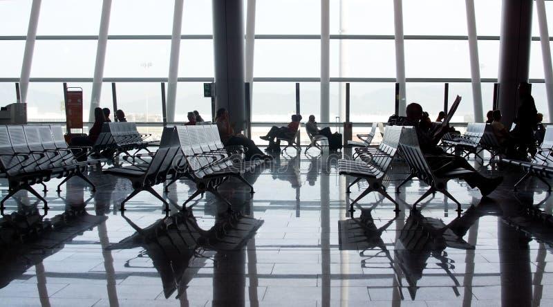 Ventana de cristal y gente grandes interiores del aeropuerto imagenes de archivo
