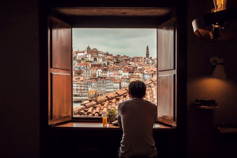 Ventana de la casa vieja del hombre joven al viejo paisaje de la ciudad con los tejados y el río foto de archivo libre de regalías