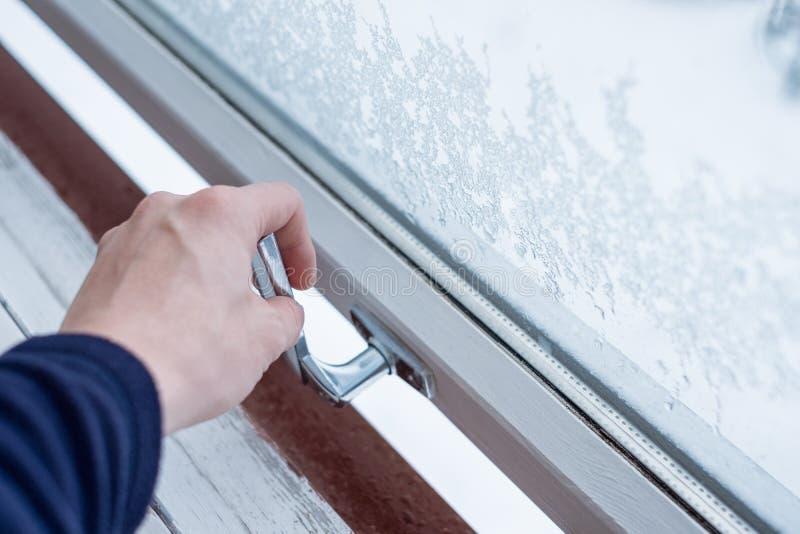 Ventana de la cerradura de abertura de la mano con la escama del hielo en invierno imagenes de archivo