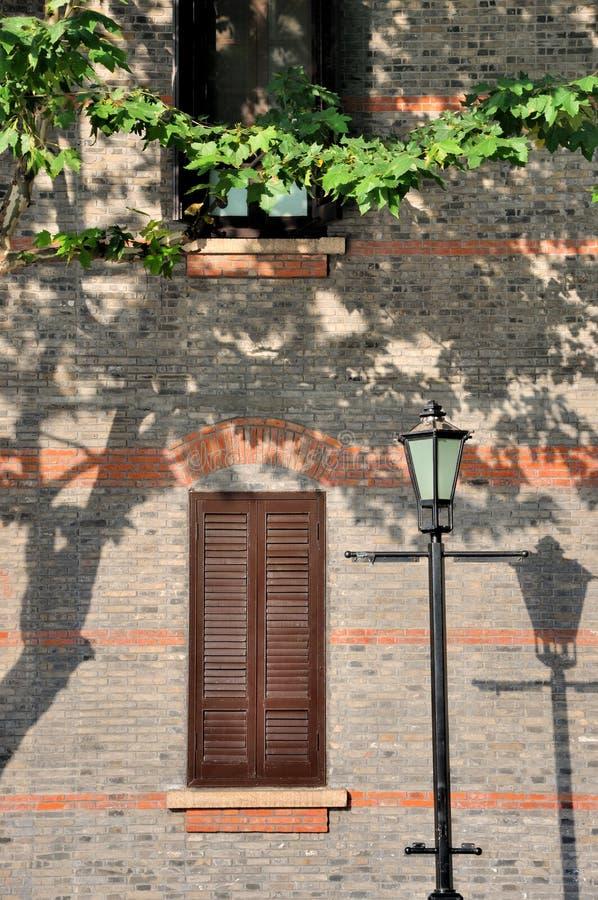 Ventana de la configuración y lámpara externas envejecidas del camino