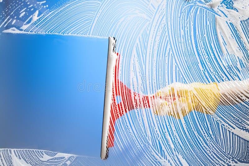 Ventana de la limpieza con el cielo azul del enjugador fotografía de archivo libre de regalías