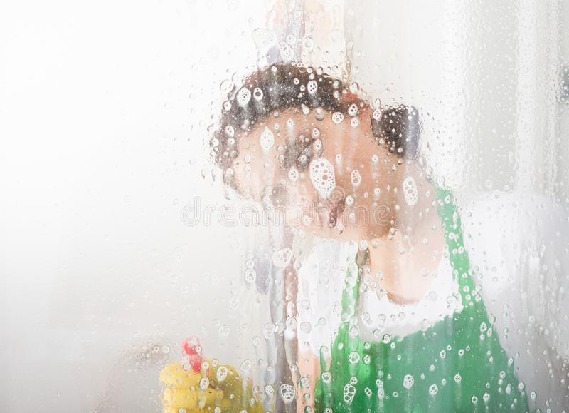 Ventana de la limpieza de la mujer de la economía doméstica con el espray foto de archivo libre de regalías