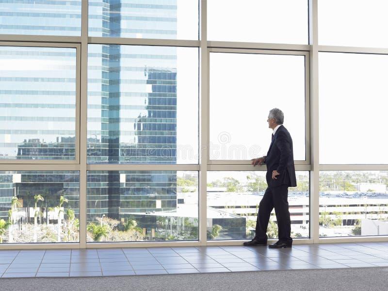 Ventana de la oficina de Looking Out Of del hombre de negocios fotografía de archivo