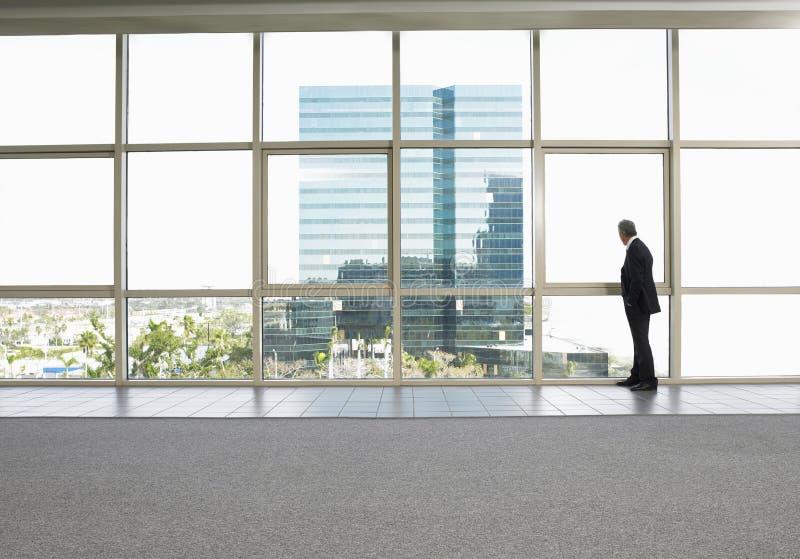 Ventana de la oficina de Looking Out Of del hombre de negocios foto de archivo