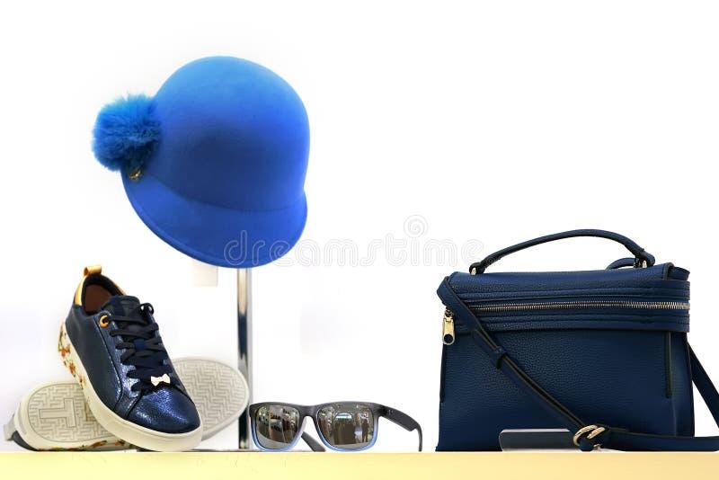 Ventana de la tienda con el bolso, el sombrero azul, las gafas de sol y las zapatillas de deporte foto de archivo